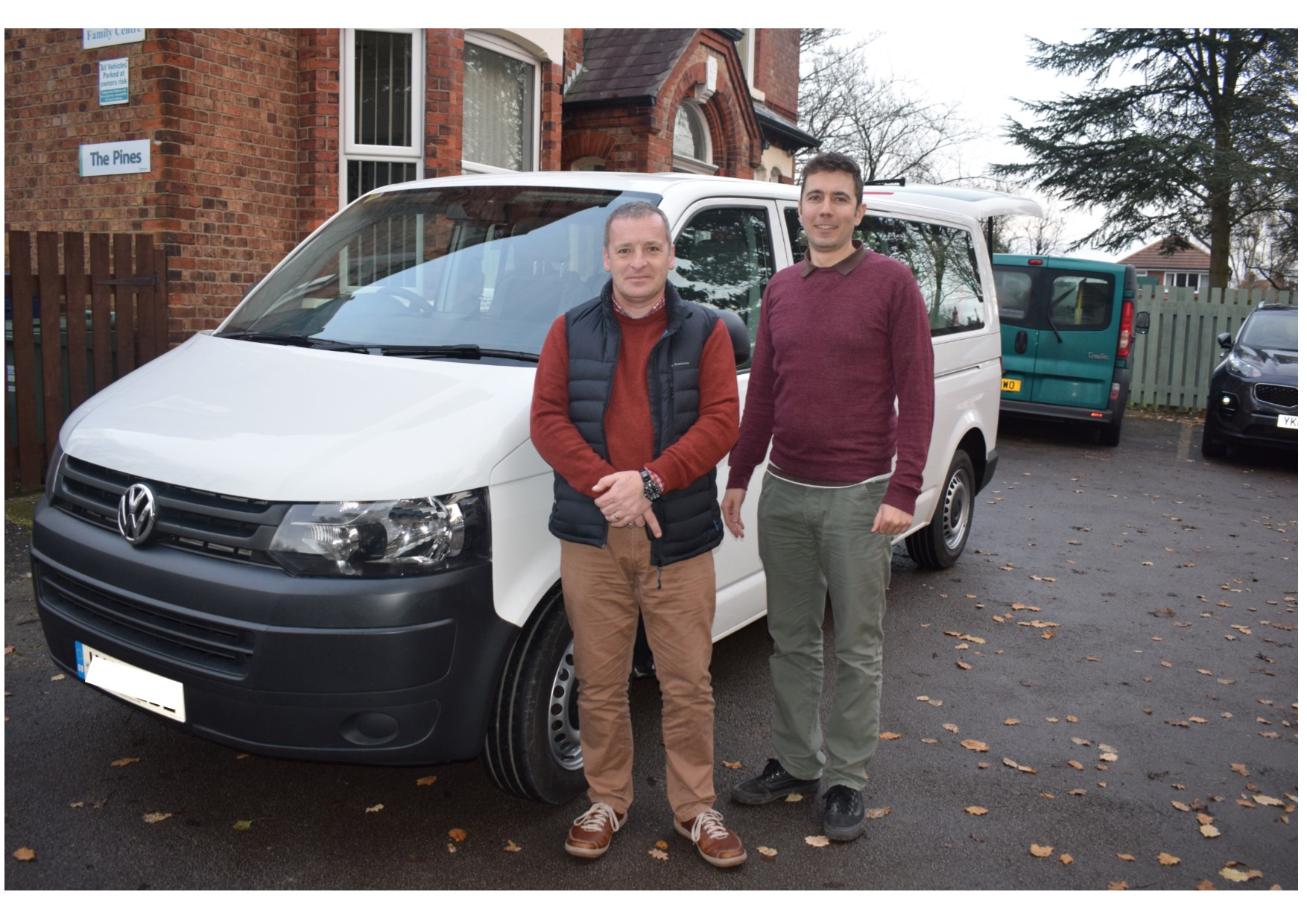 White minibus with two men standing next to it