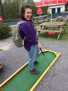 woman plays minigolf