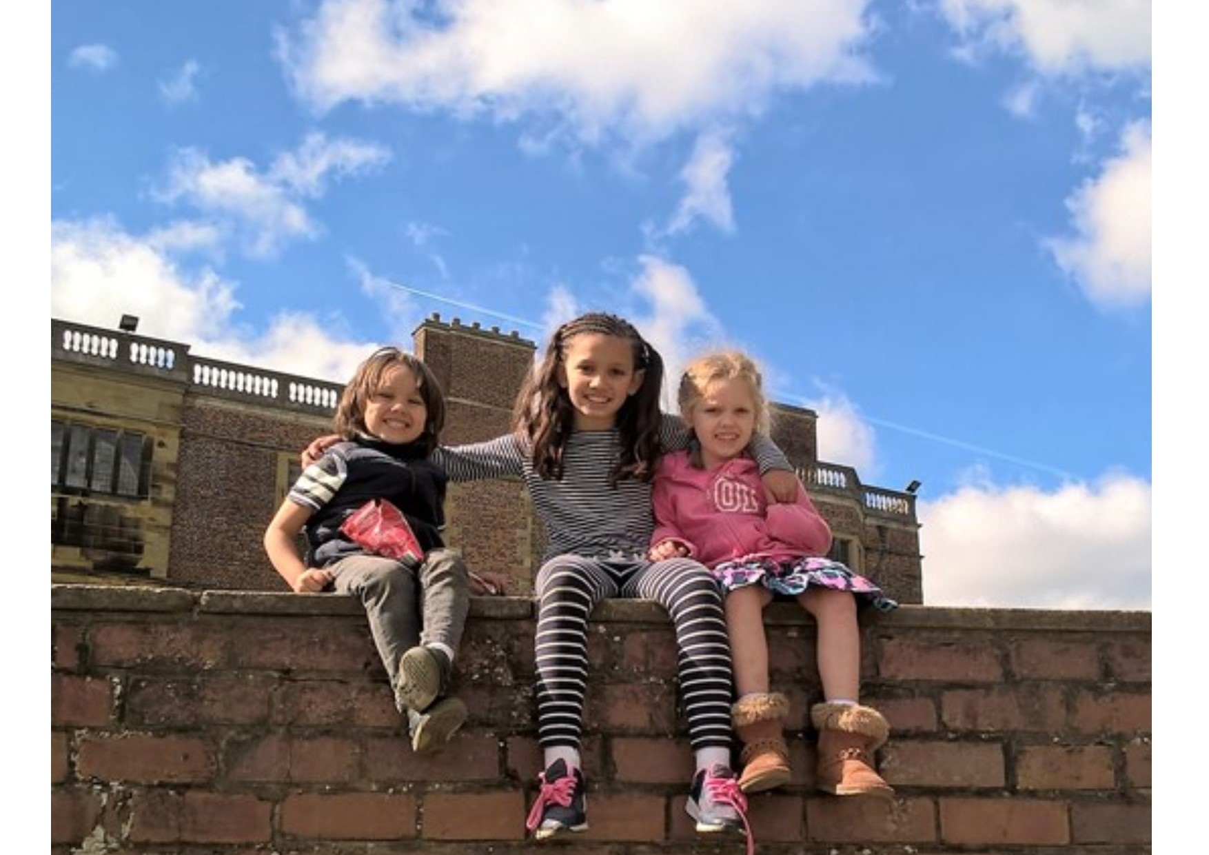 siblings climb on wall in sunshine